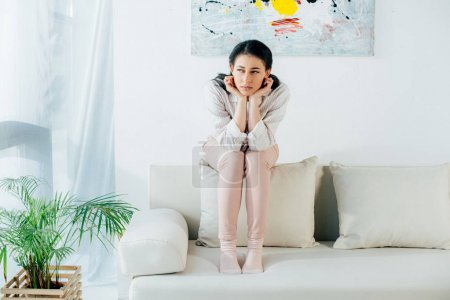 Photo for Sad latin woman sitting on back of sofa and looking away at home - Royalty Free Image