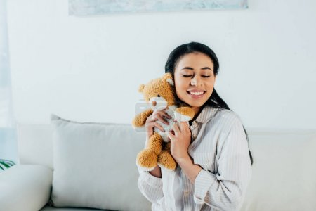 Photo for Happy latin woman with closed eyes hugging teddy bear while sitting on couch at home - Royalty Free Image