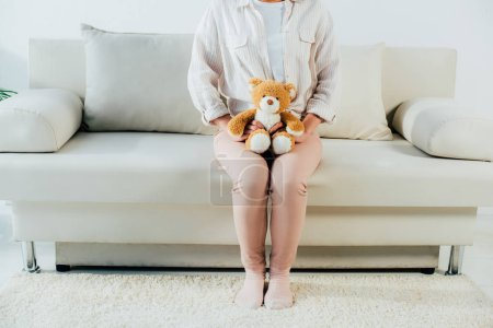 Photo for Cropped shot if young woman sitting on couch at home and holding teddy bear - Royalty Free Image