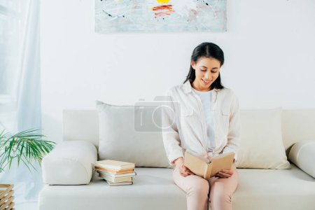 Photo for Pretty latin woman sitting on sofa at home, smiling and reading book - Royalty Free Image