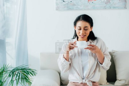 Photo for Pretty latin woman drinking coffee with closed eyes while sitting on sofa at home - Royalty Free Image
