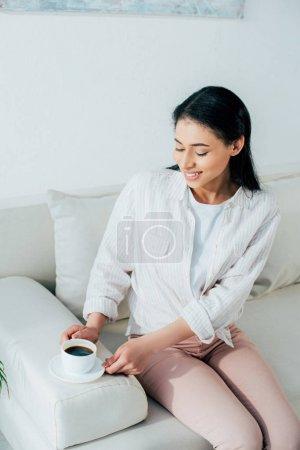 Photo pour Gaie femme latine tenant une tasse de café tout en étant assis sur le canapé à la maison - image libre de droit