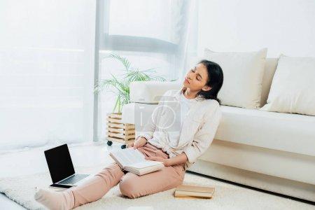 Photo pour Femme latine fatiguée retenant le livre ouvert tout en s'asseyant sur l'étage près de l'ordinateur portatif - image libre de droit