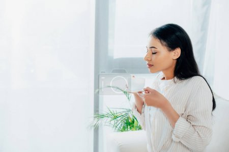 Photo for Pretty latin woman holding coffee cup with closed eyes while standing by window at home - Royalty Free Image