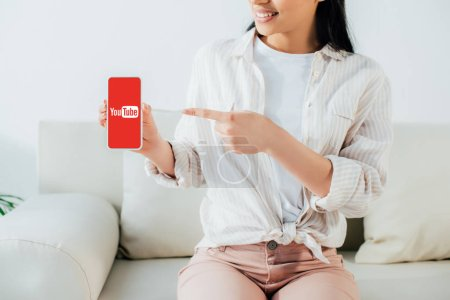 Photo for KYIV, UKRAINE - APRIL 26, 2019: Partial view of latin woman pointing with finger at smartphone with Youtube app on screen. - Royalty Free Image