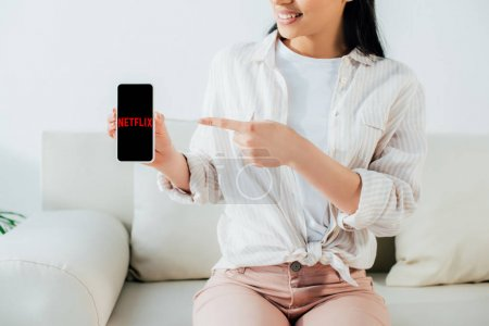 Photo for KYIV, UKRAINE - APRIL 26, 2019: Cropped shot of latin woman showing smartphone with Netflix app on screen. - Royalty Free Image