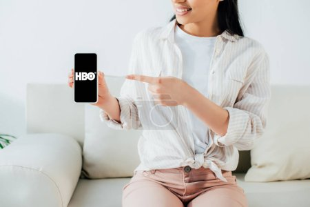 Photo pour KYIV, UKRAINE - APRIL 26, 2019: Partial view of latin woman pointing with finger at smartphone with HBO app on screen. - image libre de droit