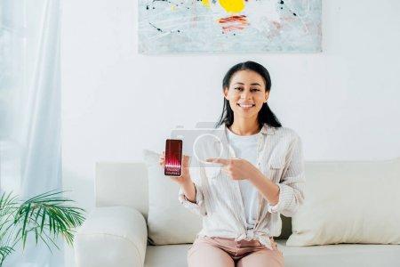 Photo pour Femme latine attirante pointant avec le doigt au smartphone avec l'application de cours de négociation à l'écran - image libre de droit