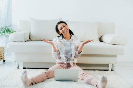 Foto de Mujer latina feliz gesturing y sonriendo a la cámara mientras se sienta en el suelo y el uso de la computadora portátil - Imagen libre de derechos