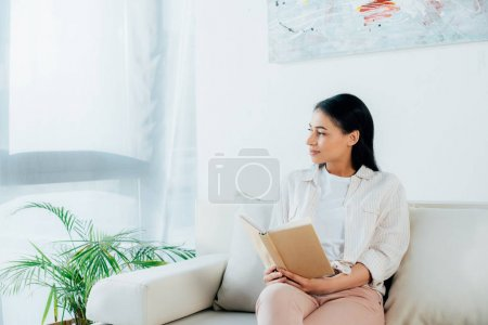Photo for Young latin woman looking away and smiling while sitting on sofa and holding book - Royalty Free Image
