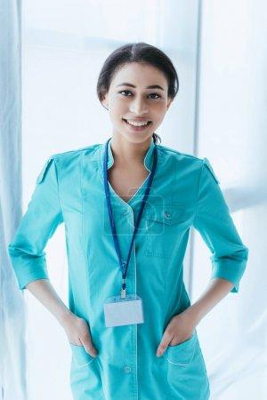 Photo pour Beau docteur latin retenant des mains dans des poches et souriant à l'appareil-photo - image libre de droit