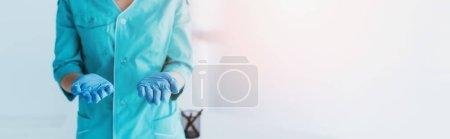 Foto panorámica de enfermera en uniforme azul y guantes de látex con palmas abiertas