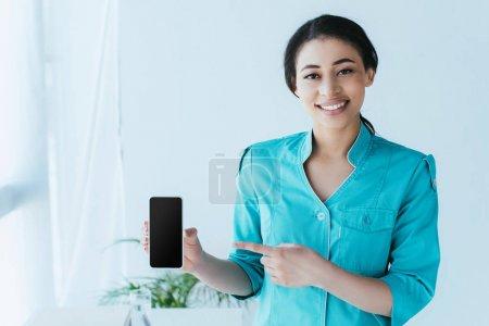 Photo pour Docteur assez latin pointant avec le doigt au smartphone avec l'écran blanc - image libre de droit