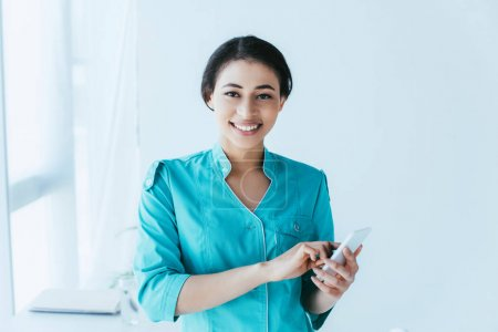 Photo for Cheerful latin nurse using smartphone and smiling at camera - Royalty Free Image