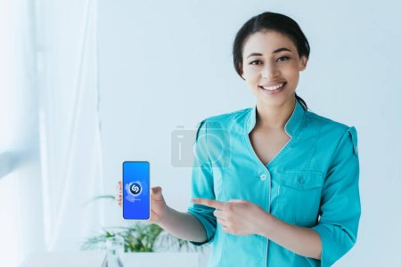 Photo for KYIV, UKRAINE - APRIL 26, 2019: Beautiful latin doctor pointing with finger at smartphone with  Shazam app on screen. - Royalty Free Image