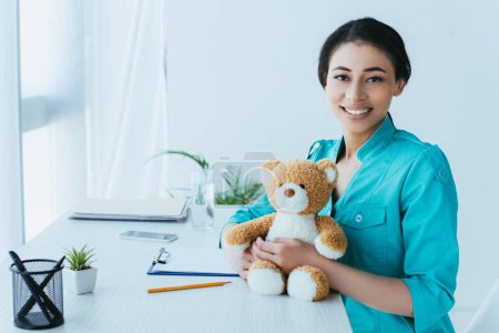 Photo for Beautiful latin doctor holding teddy bear and smiling at camera while sitting at workplace - Royalty Free Image