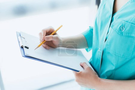 Photo for Cropped shot of doctor in blue uniform writing on clipboard - Royalty Free Image