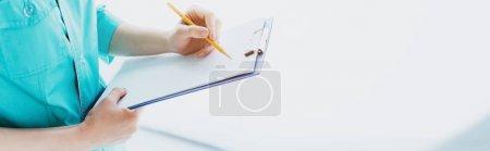 Photo pour Tir panoramique du médecin en écriture uniforme bleu sur le presse-papiers - image libre de droit