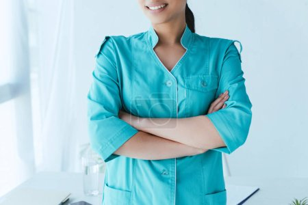 Photo for Partial view of young latin doctor standing with crossed arms near workplace - Royalty Free Image