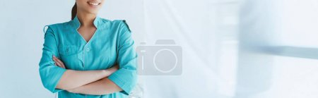 Photo for Panoramic shot of young latin nurse in blue uniform standing with crossed arms - Royalty Free Image