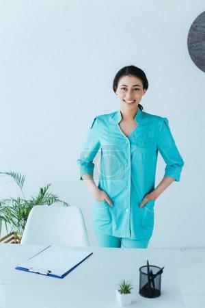 Photo pour Docteur latin attrayant souriant à l'appareil-photo tout en restant près du lieu de travail avec des mains dans des poches - image libre de droit