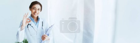 Photo for Panoramic shot of happy latin doctor showing ok gesture and holding clipboard - Royalty Free Image