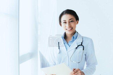 Photo pour Docteur latin gai avec le dossier de papier de fixation de stéthoscope et souriant à l'appareil-photo - image libre de droit