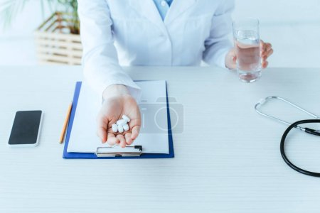 Photo for Cropped shot of young doctor with glass of water and handful of pills sitting at workplace in hospital - Royalty Free Image