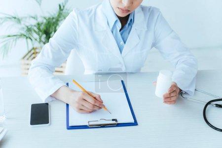 Photo pour Plan recadré de jeune médecin écrivant sur presse-papiers tout en étant assis sur le lieu de travail et tenant récipient de pilules - image libre de droit