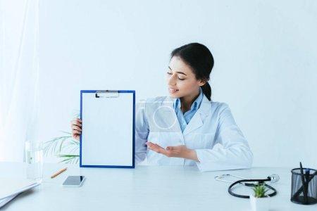 Photo pour Docteur latin souriant retenant le presse-papiers avec le papier blanc tout en s'asseyant au bureau - image libre de droit