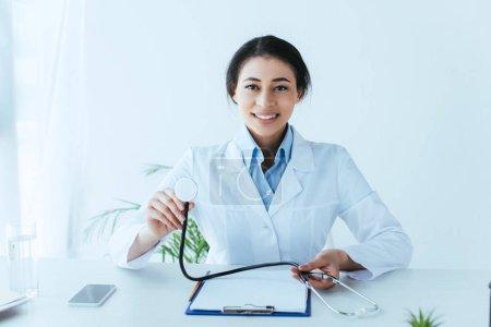 Photo pour Docteur latin souriant retenant le stéthoscope et souriant à l'appareil-photo tout en s'asseyant au lieu de travail dans la clinique - image libre de droit