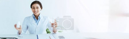 Photo for Panoramic shot of smiling latin doctor holding glass of water and container with pills - Royalty Free Image