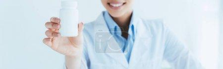 Photo pour Plan panoramique de sourire médecin latin montrant récipient avec des pilules - image libre de droit
