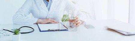Photo pour Plan panoramique du médecin tenant un verre d'eau tout en étant assis sur le lieu de travail près du presse-papiers - image libre de droit
