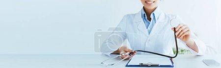 Photo pour Tir panoramique du docteur souriant retenant le stéthoscope près du presse-papiers - image libre de droit