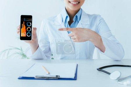 Photo pour Vue partielle du docteur latin souriant pointant avec le doigt au smartphone avec l'infographie à l'écran - image libre de droit
