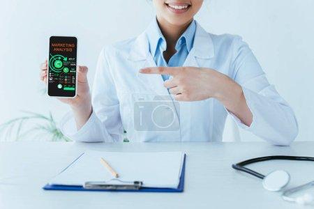 Photo pour Coup recadré de docteur latin souriant pointant avec le doigt au smartphone avec l'application d'analyse de marketing à l'écran - image libre de droit