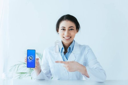 Photo pour Kiev, Ukraine - 26 avril 2019: Un médecin latin souriant pointant du doigt le smartphone avec l'application Shazam à l'écran. - image libre de droit