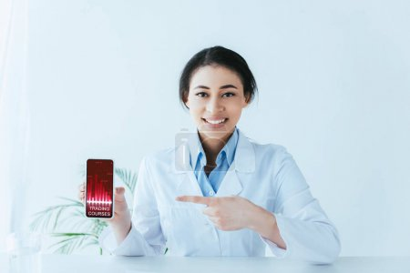Photo for Attractive latin doctor pointing with finger at smartphone with trading courses on screen - Royalty Free Image