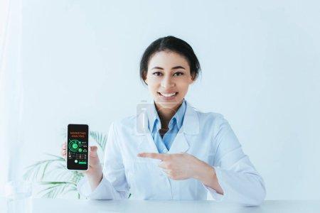 """Photo pour Jeune médecin latin pointant du doigt le smartphone avec analyse de marketing à l """"écran - image libre de droit"""