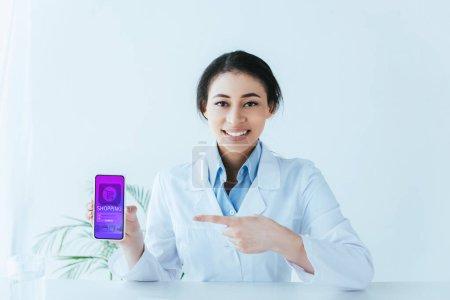 Photo pour Beau docteur latin affichant le smartphone avec l'application en ligne d'achats sur l'écran - image libre de droit