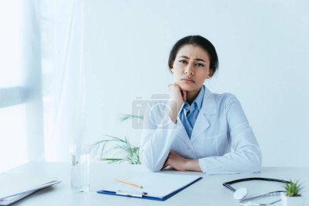 upset latin doctor looking at camera while sitting at workplace in clinic