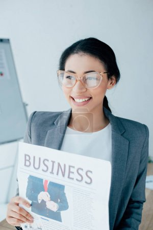 cheerful latin businesswoman holding business newspaper, smiling and looking away