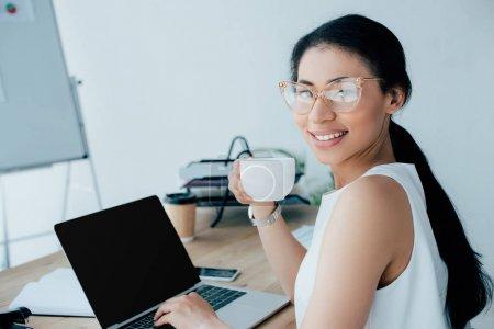 Photo pour Femme d'affaires latine gaie retenant la cuvette de café et utilisant l'ordinateur portatif tout en souriant à l'appareil-photo - image libre de droit