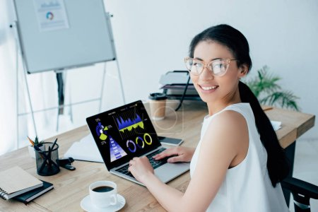 Photo for Young latin businesswoman looking at camera while using laptop with graphs and charts on screen - Royalty Free Image