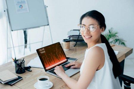 Foto de Young latin businesswoman smiling at camera while using laptop with online trade website on screen - Imagen libre de derechos