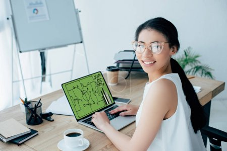 Photo for Cheerful latin businesswoman playing online football game on laptop and looking at camera - Royalty Free Image