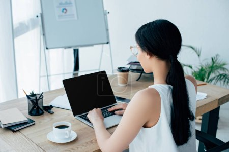 young latin businesswoman using laptop while sitting at workplace near cup of coffee