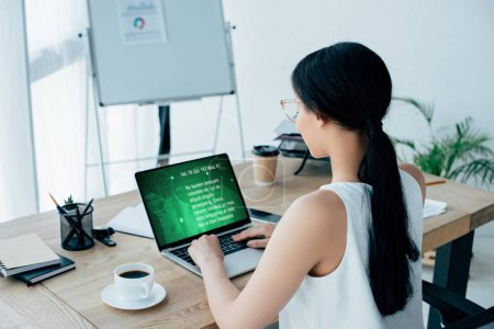 Photo pour Young latin businesswoman using laptop using laptop with text information on screen while sitting at workplace near cup of coffee - image libre de droit