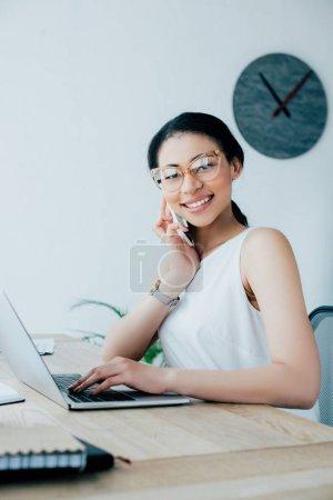 Foto de Bastante latinoamericana mujer de negocios hablando en el teléfono inteligente y el uso de la computadora portátil en el lugar de trabajo - Imagen libre de derechos